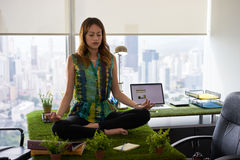 Business Woman Doing Yoga Meditation On Table In Office-2 Royalty Free Stock Image
