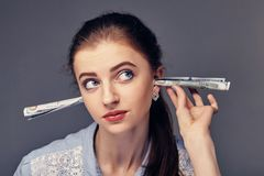 I hear only the sound of money. Business woman with dollar banknotes plugged in ears as a symbol of a desire to be. Business woman with dollar banknotes plugged Royalty Free Stock Images