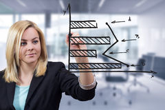 Business woman drawing horizontal bar chart at office. Business woman drawing horizontal bar chart on transparent surface at office Royalty Free Stock Photo