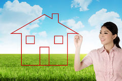 Business woman drawing house on the meadow Royalty Free Stock Images