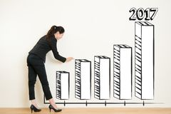 Business woman drawing over target achievement graph Royalty Free Stock Image