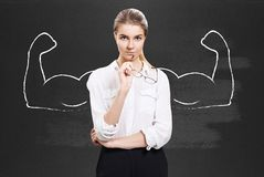 Business woman with drawn powerful hands. Business woman stands over chalkboard with drawn powerful hands Stock Image