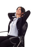 Business woman dreaming. A business woman leaning back in a black chair dreaming Stock Image