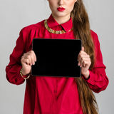 Business woman dressed in red holding and shows touch screen tablet pc with blank screen Royalty Free Stock Images
