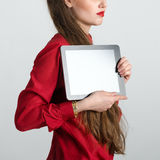 Business woman dressed in red holding and shows touch screen tablet pc with blank screen Royalty Free Stock Image