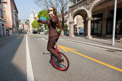 Business woman drink a coffee on the unicycle Stock Photo