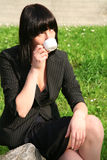 Business woman drinking coffee. The business woman drinks coffee in park Royalty Free Stock Images