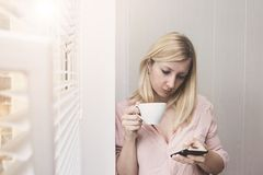 Business woman drinking coffee in the morning sun and using smartphone stock photos
