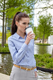 Business woman drinking coffee in a park Royalty Free Stock Photography