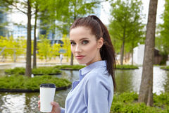 Business woman drinking coffee in a park Stock Photo
