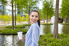 Business woman drinking coffee in a park Royalty Free Stock Image