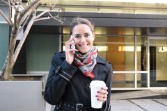 Business woman drinking coffee and talking on the phone Stock Image