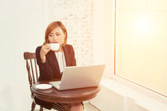 Business woman drinking coffee and using laptop  in office Stock Photography
