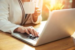 Business woman drinking a cup of coffee. And using her laptop for working in some bright morning Royalty Free Stock Photography