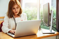 Business woman drinking a cup of coffee and using her laptop. For working in some bright morning Royalty Free Stock Photo