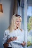 Business woman drinking and staring out of window Royalty Free Stock Images