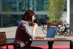 Business woman drinking tea and using laptop at cafe Stock Photo