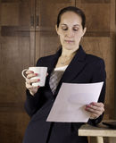 Business woman drinks coffee and reads Royalty Free Stock Image