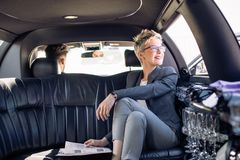 A business woman is driving in a limousine Stock Photography