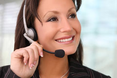 Business Woman With Earphone. A pretty business woman with earphone communicating at office Royalty Free Stock Image