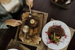 Business woman eating beef steak with butter in a restaurant on wooden table. Dinner time of healthy food. View from above stock photos