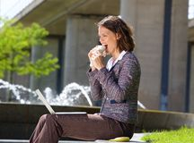 Business woman eating food during lunch break. Side portrait of a business woman eating food during lunch break royalty free stock photo