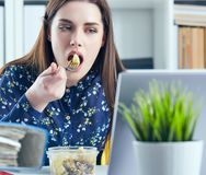 Business woman eating lunch at her workplace looking at the laptop screen. Folders with documents in the foreground. Business woman eating lunch at her workplace stock photography