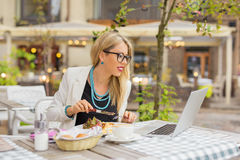 Business woman eating lunch and working on laptop. At cafe royalty free stock photo