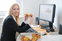 Business woman eating pizza at computer Royalty Free Stock Photo