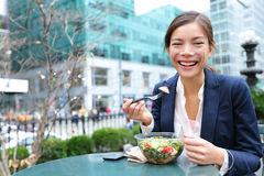Business woman eating salad on lunch break. In City Park living healthy lifestyle. Happy smiling multiracial young businesswoman, Bryant Park, Manhattan, New royalty free stock image