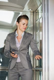 Business woman in elevator pushing button Royalty Free Stock Images