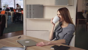 Business Woman Ending Project and Relax With Cup Of Tea. Female office modern and light with big wooden table. On the wall shelves with documents in folders stock footage