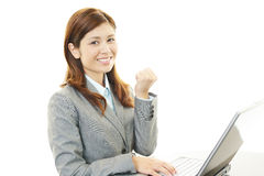 Business woman enjoying success. Asian business woman sitting at desk working on laptop Royalty Free Stock Images