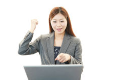 Business woman enjoying success. Asian business woman sitting at desk working on laptop Royalty Free Stock Image
