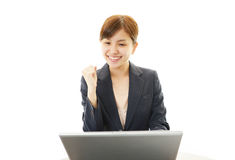 Business woman enjoying success. Asian business woman sitting at desk working on laptop Royalty Free Stock Photos