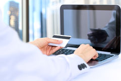 Business woman  entering  data of  a credit card . On-line shopping on the internet using a laptop Stock Photos