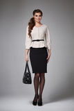 Business woman evening makeup clothes for meetings and walks. Beautiful young business woman with evening make-up wearing a skirt to the knee and a silk blouse stock photo