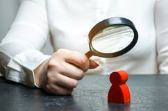 Business woman examines a red man`s figure through a magnifying glass. Analysis of the personal qualities of the employee. Characteristic. Unreliable employee royalty free stock photography