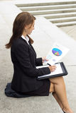 Business woman examines report document and writes in notebook Stock Image