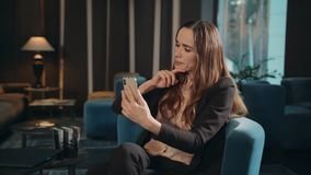 Business woman examining face makeup looking at smartphone in cafe. Businesswoman touching hair in front of mobile camera in hotel lobby. Serious woman looking stock video