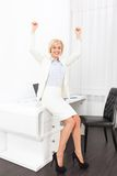 Business woman excited hands up raised arms. Business woman excited hold fist hands up raised arms sitting at modern office desk, surprised happy smile Stock Photos