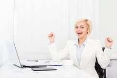 Business woman excited at modern office desk. Business woman excited hold fist hands up raised arms sitting at modern office desk, surprised happy smile Stock Photo