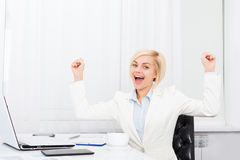 Business woman excited at modern office desk Royalty Free Stock Photography