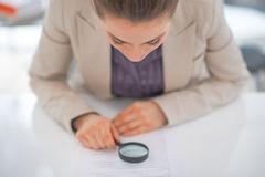 Business woman exploring document. With magnifying lens Stock Photo