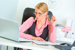 Business woman in eye glasses working on laptop Stock Photos