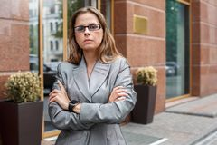 Business woman in eyeglasses standing on the city street crossed arms impudent stock image