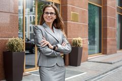 Business woman in eyeglasses standing on the city street crossed arms looking camera cheerful royalty free stock image