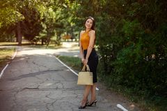 Business woman with a fashionable bag in her hands posing on the nature in the park. royalty free stock photography