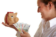Business woman feeding piggy bank Stock Photos