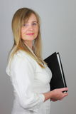 Personal Assistant with file folder. Blond middle aged woman carrying a black file folder; neutral background Royalty Free Stock Photo
